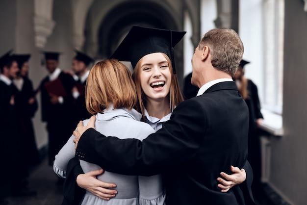Die eltern gratulieren dem schüler, der das studium beendet hat.
