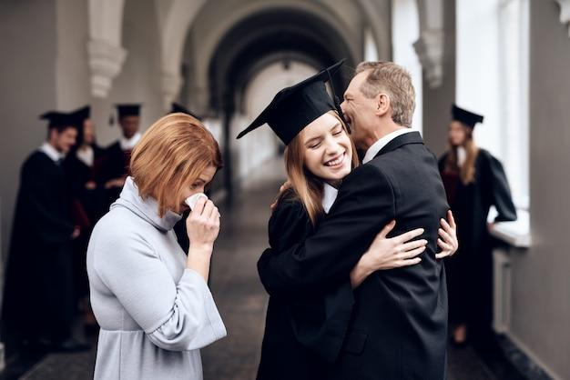 Die eltern gratulieren dem schüler, der sein studium beendet hat.