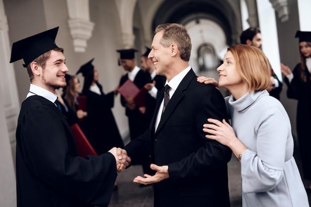 Die eltern gratulieren dem schüler, der sein studium beendet hat