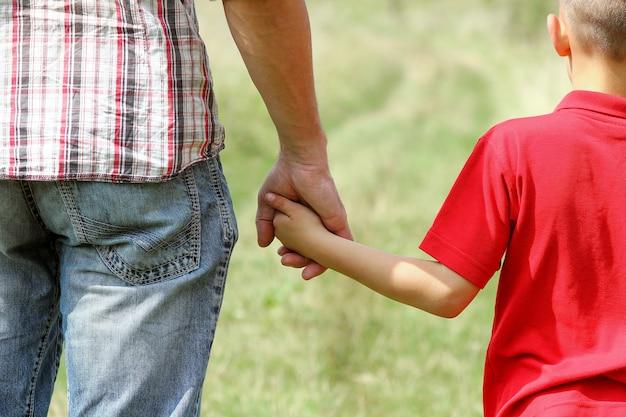 Die eltern halten die hand eines kleinen kindes an der natur