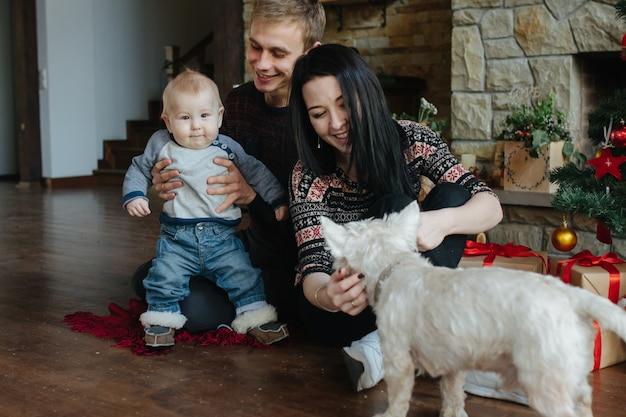 Die eltern und ein baby spielt mit dem hund
