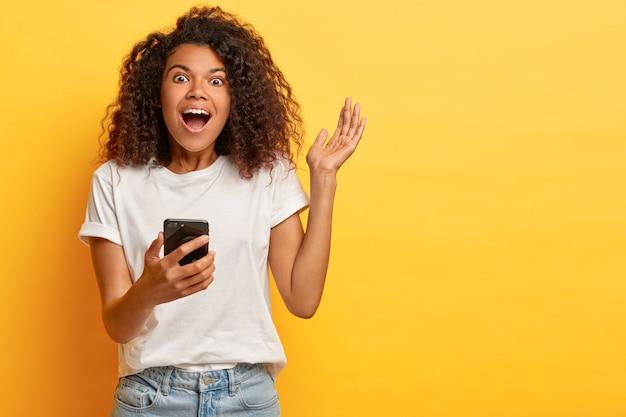 Die energiegeladene emotionale afro-frau lacht, als sie unterhalten und amüsiert ist, hält ein modernes handy in der hand, hebt den arm, trägt ein weißes t-shirt und jeans, hält den atem vor erstaunen, isoliert an der gelben wand