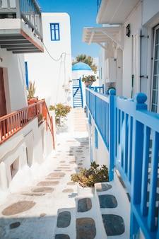 Die engen gassen der insel mit blauen balkonen, treppen und blumen in griechenland.