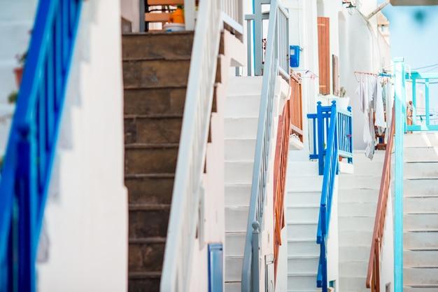 Die engen gassen der insel mit blauen balkonen, treppen und blumen.