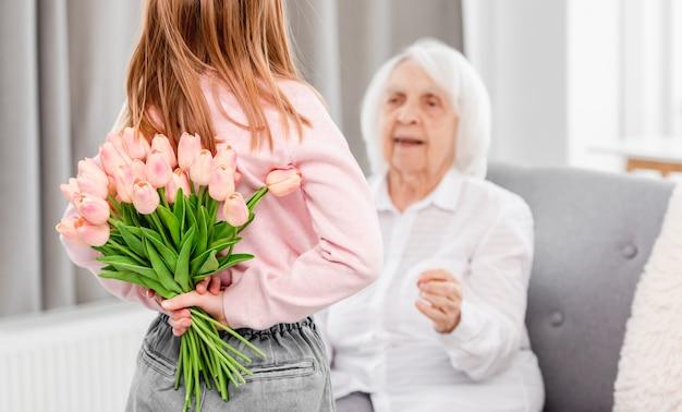 Die enkelin im vorschulalter überrascht die großmutter und hält den tulpenstrauß hinter ihren rücken