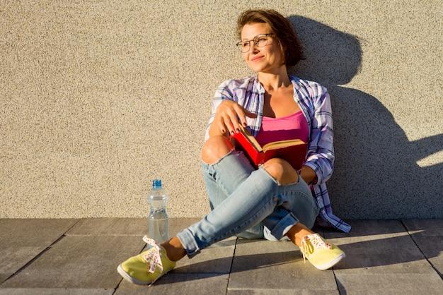 Die entspannende erwachsene frau sitzen auf dem bürgersteig