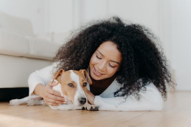 Die entspannte afrofrau mit dem klaren dunklen haar liegt auf dem boden, spielt mit dem netten welpen, hat spaß mit dem terrierhund jack russell, der die weiße strickjacke trägt, die im wohnzimmer ist