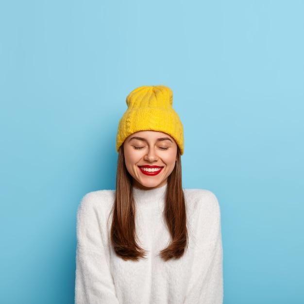 Die entzückende dunkelhaarige frau hat ein minimales make-up, einen roten lippenstift, lächelt angenehm, trägt einen gelben hut und einen weißen pullover, isoliert über der blauen wand