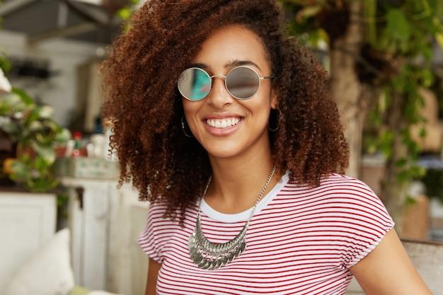 Die entzückende, dunkelhäutige, lächelnde, süße frau mit afro-frisur trägt eine modische sonnenbrille, genießt die sommererholung, sitzt gegen das café-interieur und hat ein angenehmes gespräch mit einem freund, der gegenüber sitzt