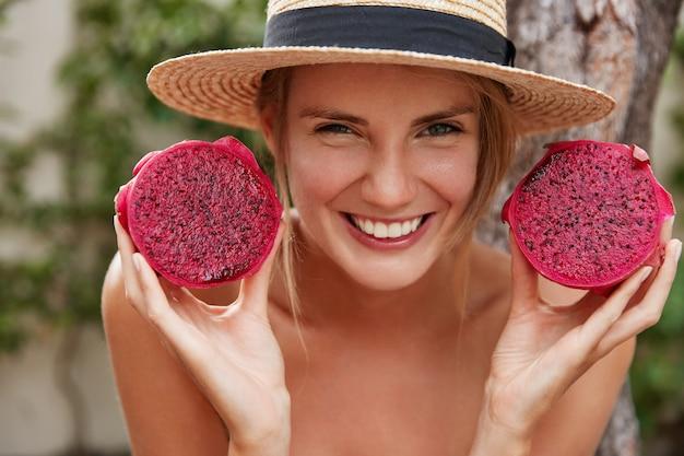 Die entzückende fröhliche junge frau, die froh ist, unvergessliche sommerferien in den tropen zu verbringen, hält drachenfrucht in händen