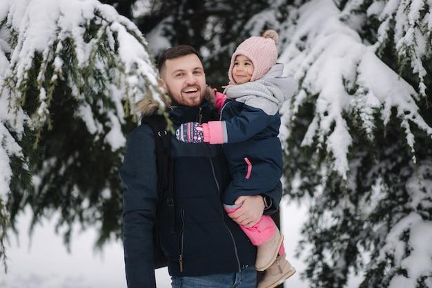 Die entzückende kleine tochter mit ihrem schönen vater steht neben dem großen schneebedeckten baum