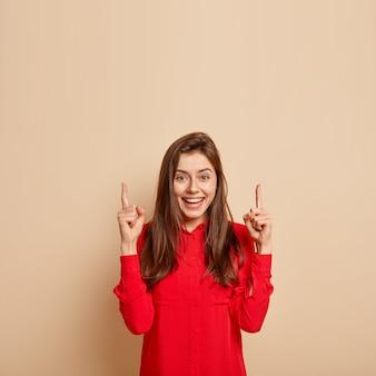 Die entzückende schöne junge frau zeigt nach oben, sieht beeindruckt und fasziniert aus, trägt ein rotes modisches hemd, zeigt einen gegenstand an der beigen wand und zeigt eine leerstelle für ihre werbung