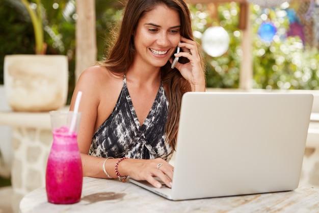 Die entzückende selbständige junge frau sitzt vor einem geöffneten modernen laptop, arbeitet in den sommerferien aus der ferne, lässt sich vom kollegen per handy beraten, trinkt frischen cocktail oder smoothie
