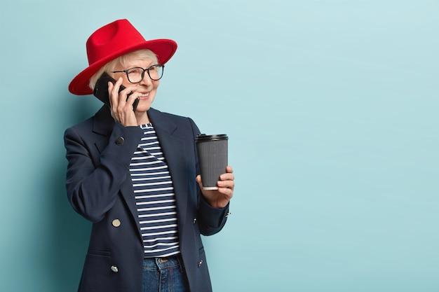 Die erfolgreiche erfolgreiche senior-geschäftsfrau führt ein smartphone-gespräch, bespricht die zeit des treffens mit dem partner, hält kaffee zum mitnehmen, schaut zur seite, hat einen fröhlichen ausdruck, steht über der blauen wand
