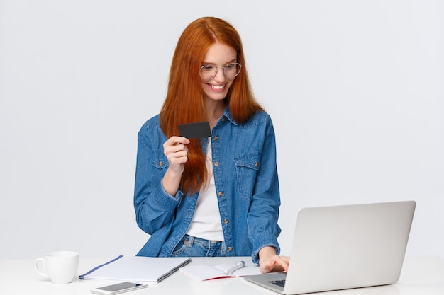 Die erfreute, erfüllte entspannte nette rothaarigefrau, die auftrag von der arbeit, online zahlend macht, fügen rechnungsinformationen der kreditkartennummer ein und verwenden den laptop, um zu kaufen und stehen weiß