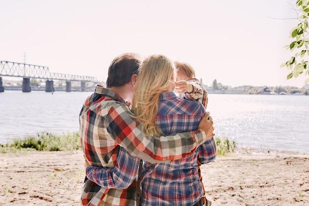 Die erinnerungen, die wir mit unserer familie machen, sind alles, was eine glückliche familie in einem park umarmt