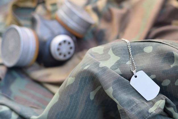 Die erkennungsmarke mit der sowjetischen gasmaske der stalkersoldaten liegt auf grünen khaki-tarnjacken