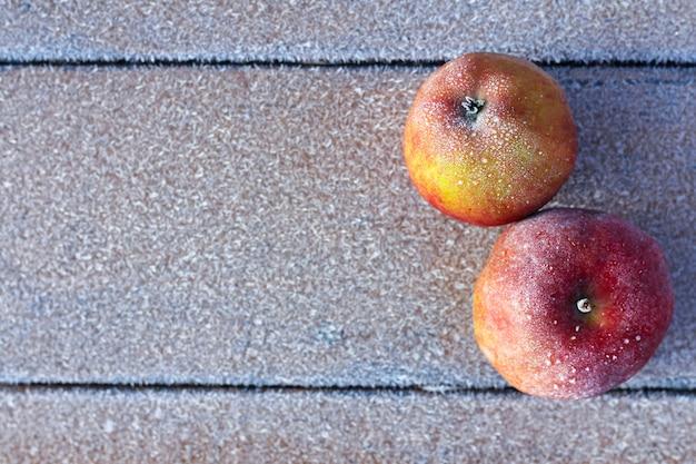 Die ersten fröste im spätherbst. die äpfel und das ahornblatt waren mit frost bedeckt. herbsthintergrund, draufsicht