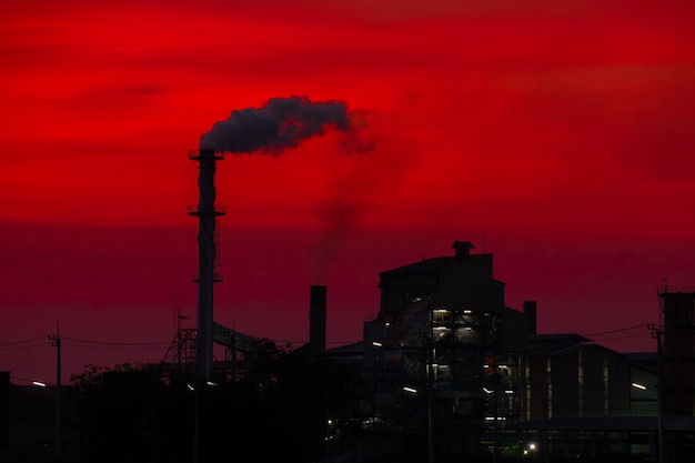Die fabrik gab rauchschornstein in der globalen erwärmung des sonnenuntergangs frei