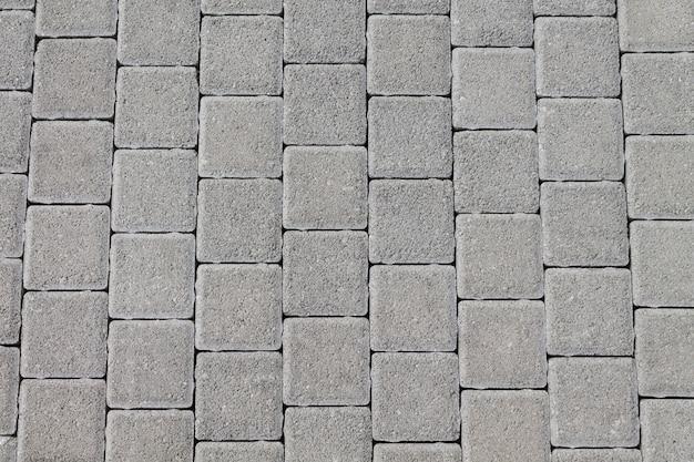 Die fahrbahn besteht aus naturstein in form von quadratischen fliesen. textur natürliches design