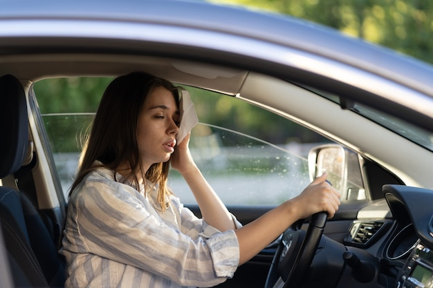 Die fahrerin, die während der hitzewelle im auto unter heißem wetter leidet, wischt schweiß von der stirn