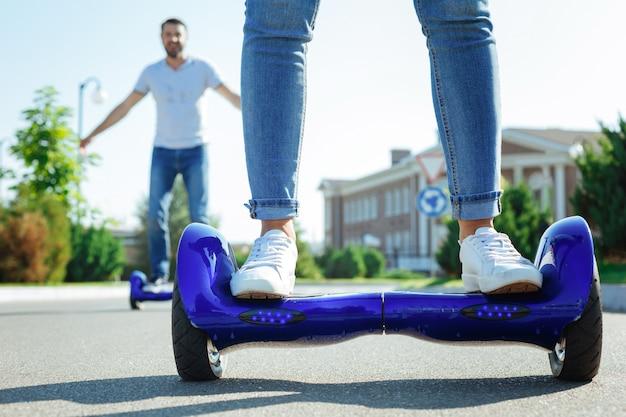 Die fahrt genießen. die nahaufnahme von weiblichen beinen in jeans, die auf einem blauen hoverboard stehen, während ein fröhlicher mann, der das gleiche im hintergrund reitet