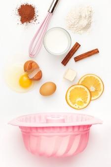 Die fallenden zutaten von kuchen oder torte auf weiß