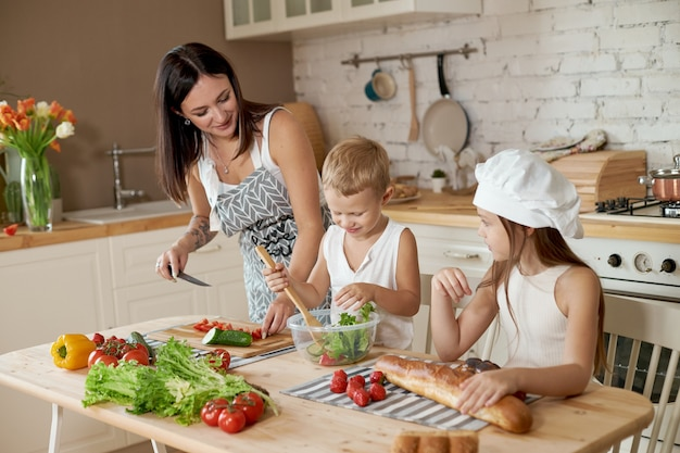 Die familie bereitet das mittagessen in der küche vor. mutter bringt ihrer tochter und ihrem sohn bei, einen salat mit frischem gemüse zuzubereiten. gesunde natürliche nahrung, vitamine für kinder