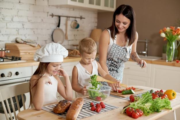 Die familie bereitet das mittagessen in der küche vor. mutter bringt ihrer tochter und ihrem sohn bei, einen salat mit frischem gemüse zuzubereiten