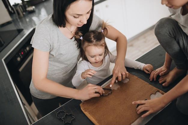 Die familie bereitet lebkuchen in der küche zu. vater, mutter, sohn, tochter, bruder und schwester. teig kneten, ausstechformen, neujahr, weihnachten, feiertagsessen. graue hauskleidung.