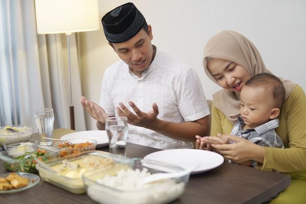 Die familie betet vor dem gemeinsamen abendessen