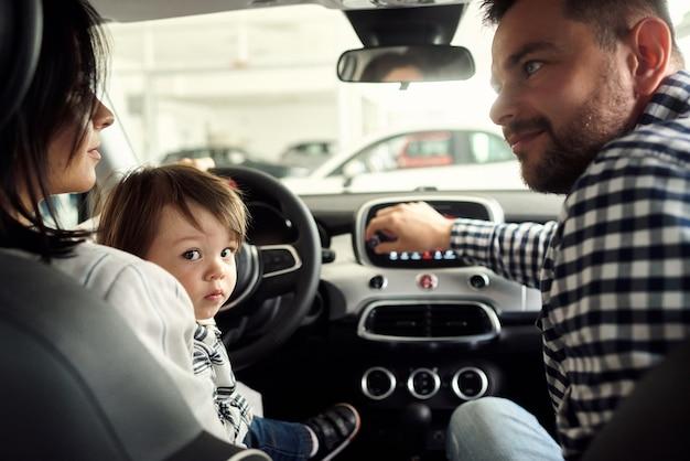 Die familie denkt über den innenraum ihres zukünftigen autos nach.