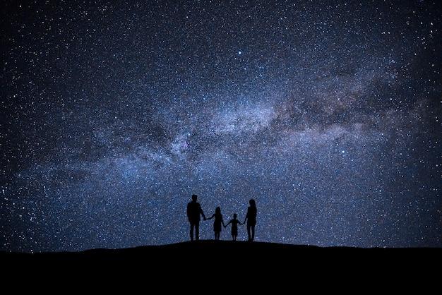 Die familie, die auf dem malerischen sternenhimmelhintergrund steht