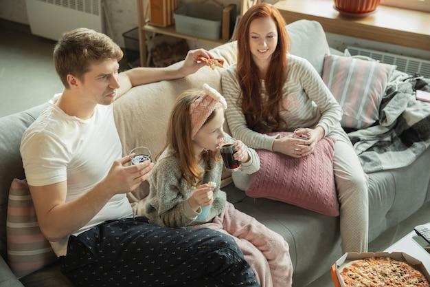Die familie, die zu hause schöne zeit miteinander verbringt, sieht glücklich und fröhlich aus