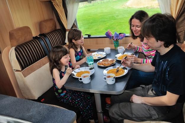 Die familie, die zusammen in rv-innenraum isst, reisen in wohnmobil (camper, wohnwagen) im urlaub