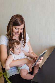 Die familie einer mutter und eines kindes mit einem elektronischen tablet zu hause