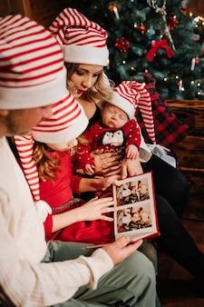 Die familie schaut sich die fotos im album in der nähe des weihnachtsbaums an