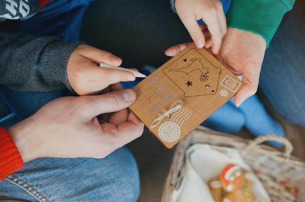 Die familie schreibt einen brief an den weihnachtsmann. hände halten eine hölzerne postkarte.