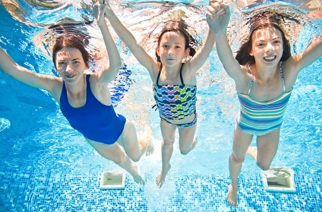 Die familie schwimmt im schwimmbad unter wasser