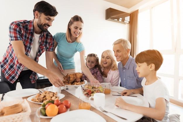 Die familie setzt sich zum abendessen an thanksgiving.