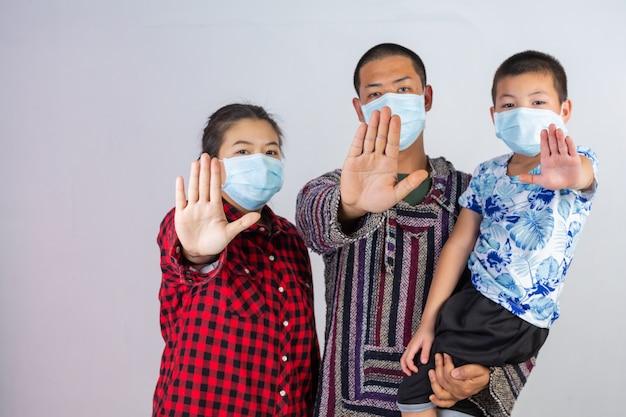 Die familie trägt eine medizinische schutzmaske