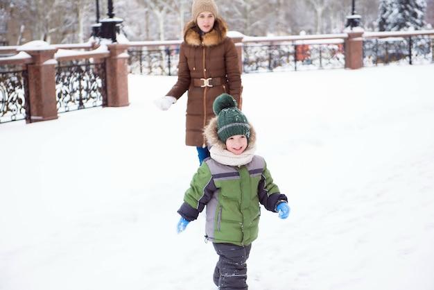 Die familienmutter- und -kindertochter, die spaß hat und am winter spielt, gehen draußen