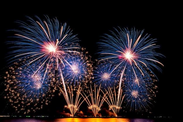 Die farbe und schönheit von feuerwerkskörpern, die nachts im meer, am schwarzen himmel aufgestellt wurden, um das fest der feiertage zu feiern, für menschen und ein frohes neues jahr.