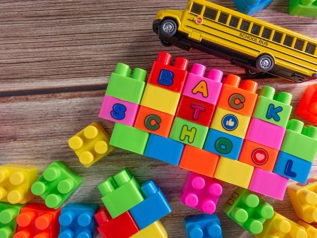 Die farbspielzeugziegel und der schulbus auf holztisch für hintergrund- oder bildungskonzept