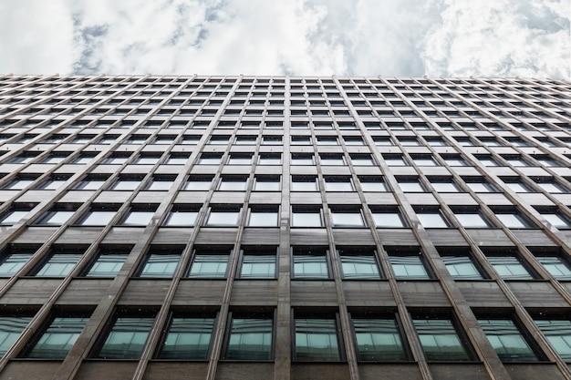 Die fassade des bürogebäudes schuss von unten nach oben mit einem horizontalen streifen von grauem himmel mit wolken. das fenster des business centers spiegelt das angrenzende gebäude wider