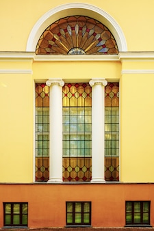 Die fassade eines alten gebäudes mit buntglasfenstern und säulen. die architektur