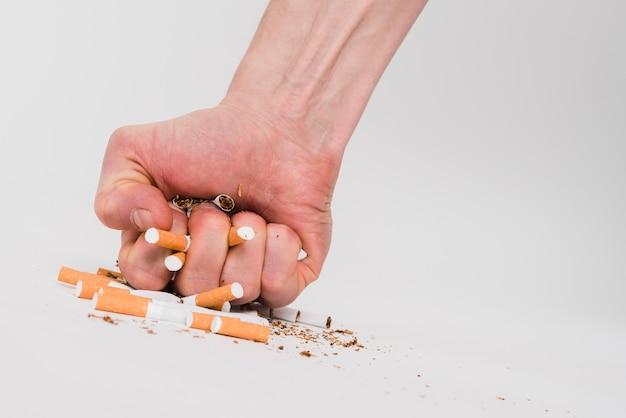 Die faust eines mannes, die zigaretten über weißem hintergrund zerquetscht