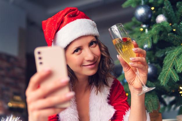 Die feier des neuen jahres und weihnachten auf der distanz des konzepts. junge frau in einem weihnachtsmann-anzug und -hut hält ein smartphone vor dem hintergrund eines verzierten tannenbaums.