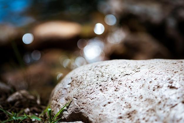 Die felsbrocken auf dem gras reflektieren das wasser als kreisförmiges bokeh für einen hintergrund.