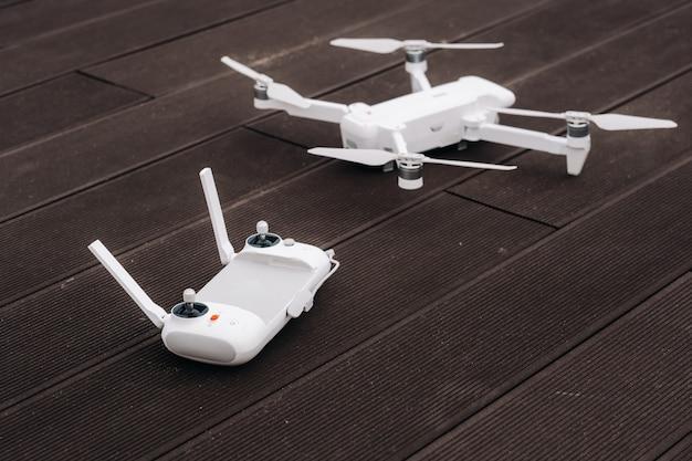 Die fernbedienung mit dem quadcopter ist weiß und der quadcopter selbst ist auf holz